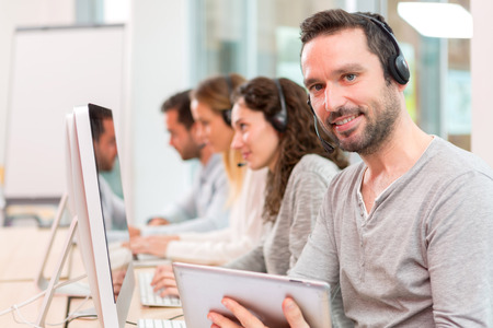 co workers: View of a Young attractive man working in a call center Stock Photo