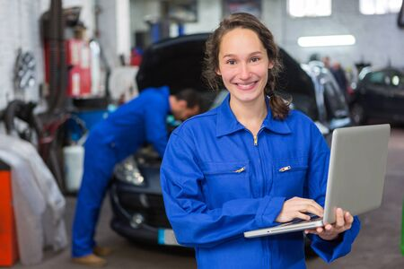 garage: View of a Young attractive woman mechanic working at the garage