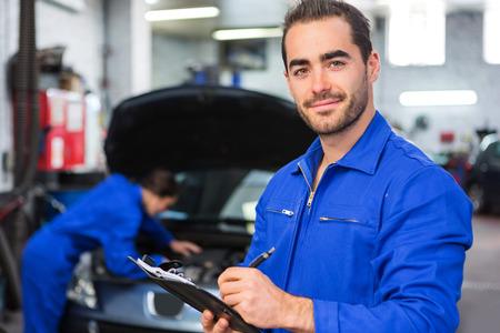 Mening van een jonge aantrekkelijke monteur werken bij de garage
