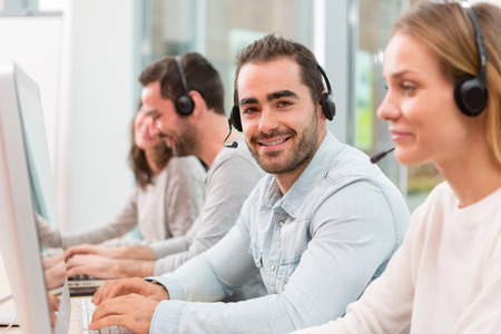 customer support: View of a Young attractive man working in a call center Stock Photo