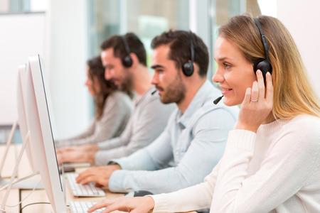 centro de computo: Vista de una mujer atractiva joven que trabaja en un centro de llamadas