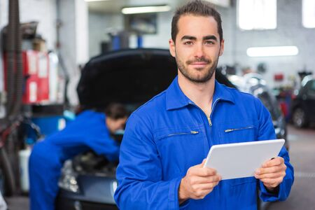 View of a Young attractive mechanic working at the garage Stock Photo