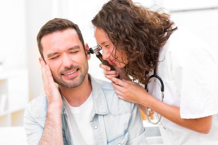 dolor de oido: Vista de un médico atractiva joven que controla el oído del paciente
