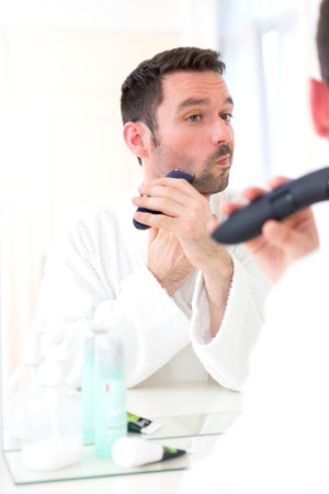 View of a Young attractive man shaving his beard in front of a mirror