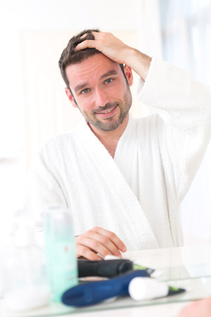 View of aYoung attractive man taking care of his hair Stock Photo