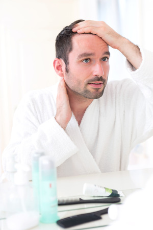 taking care: View of aYoung attractive man taking care of his hair Stock Photo