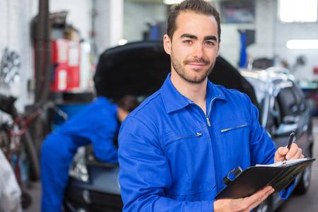 mecanico: Vista de un mec�nico atractiva joven que trabaja en el garaje Foto de archivo