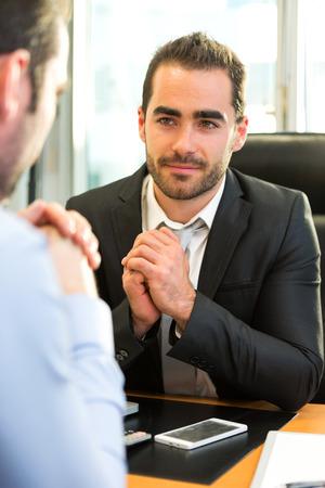 reunion de trabajo: Vista de un jefe atractivo entrevista haciendo con su asistente