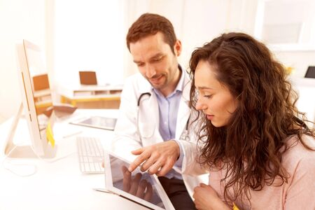 inform: View of a  Doctor using tablet to inform patient