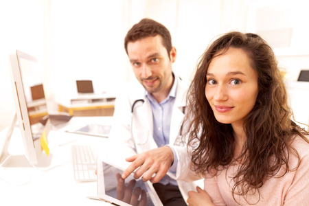 informing: View of a  Doctor using tablet to inform patient