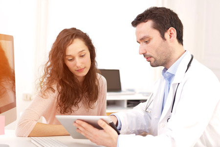 View of a  Doctor using tablet to inform patient