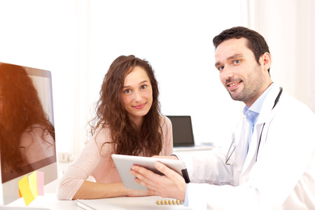 hmo: View of a  Doctor using tablet to inform patient