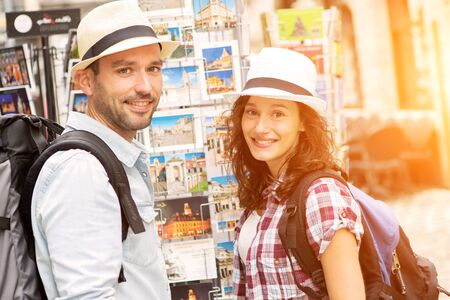 cheerfull: View of a Young happy couple choosing postcards during holidays