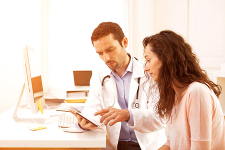 doctor's office: View of a  Doctor using tablet to inform patient