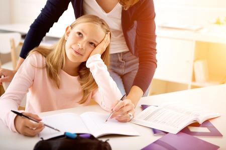 Vue d'une femme aidant sa petite soeur pour les devoirs
