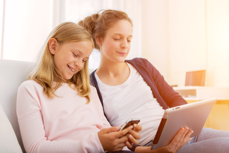 keep watch over: View of a Attractive woman and little sister using tablet Stock Photo