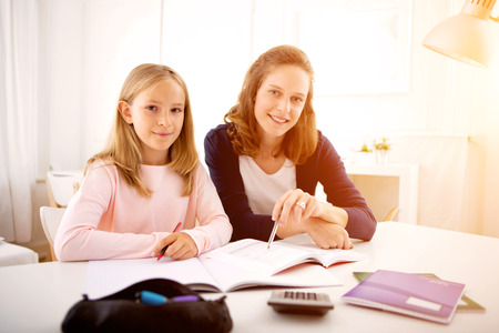 View of a Woman helping out her little sister for homework