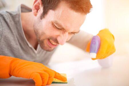 limpieza  del hogar: Vista de un hombre atractivo joven que limpia su piso Foto de archivo