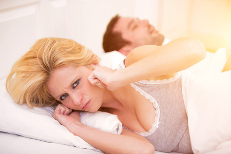 snoring: View of a Young woman cant sleep because of boyfriends snoring Stock Photo