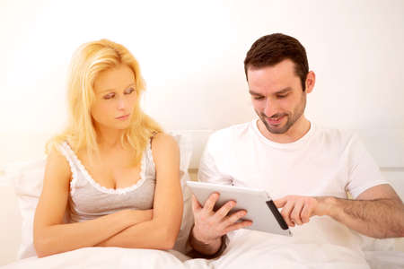 sleeping tablets: View of a Young attractive couple using mobile and tablet in bed