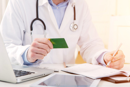 medecine: View of a Young attractive doctor taking health insurance card