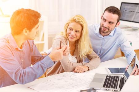 Blick auf eine junge ernste Paar Treffen ein Immobilienmakler Standard-Bild