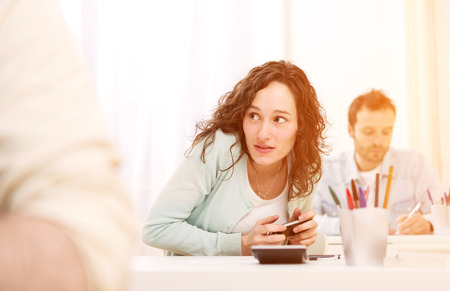 cheating woman: View of a Young attractive woman cheating with mobile during exam Stock Photo