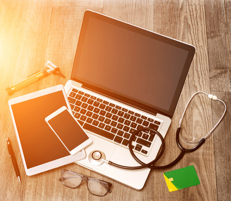 medecine: View of a Wood doctors desk in high definition with laptop, tablet and mobile phone