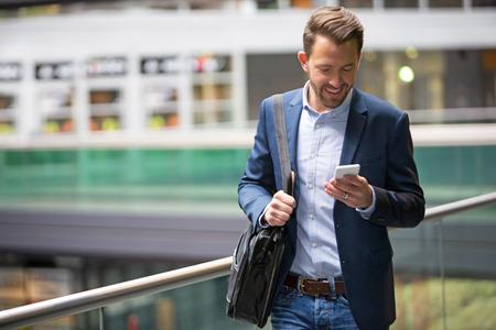 Blick auf eine junge attraktive Geschäftsmann unter Verwendung des smartphone