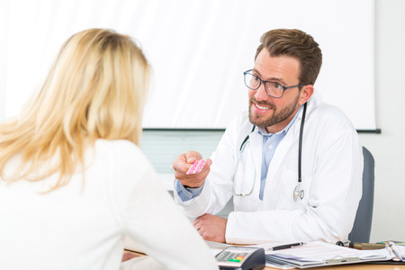 doctor giving pills: View of a Young attractive doctor giving pills to a patient