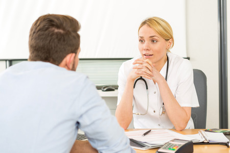 a lady doctor: View of a Young attractive woman doctor listening his patient Stock Photo