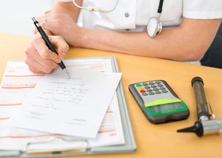 Weergave van een arts die een voorschrift aanvult aan een patiënt Stockfoto