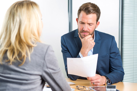 employer: View of a Young attractive employer analysing resume of woman Stock Photo