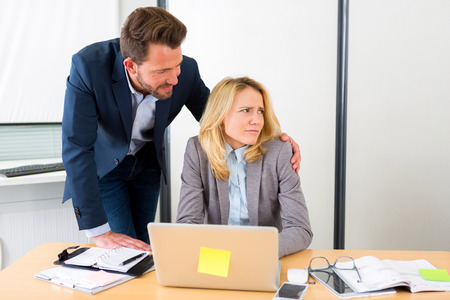acoso laboral: Vista de un jefe que pone la mano en el hombro asistente - acoso