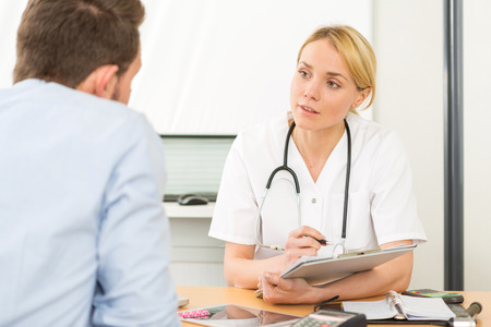 medecine: View of a Young attractive woman doctor taking notes while patient speak