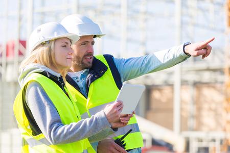 Ansicht von zwei Arbeiter arbeiten außerhalb mit einer Tablette auf einer Baustelle Standard-Bild