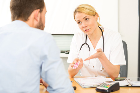 doctor giving pills: View of a Young attractive woman doctor giving pills to a patient