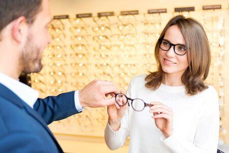 Vue d'une jeune femme séduisante tester de nouveaux verres avec opticien