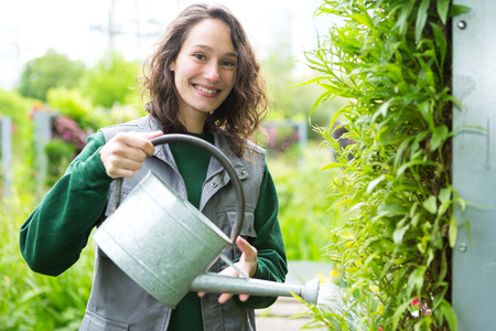garden city: VIew of a Young attractive woman working in a public garden watering flowers Stock Photo