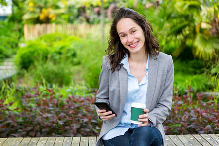 business woman working: View of a Young attractive business woman working at the park during a pause Stock Photo