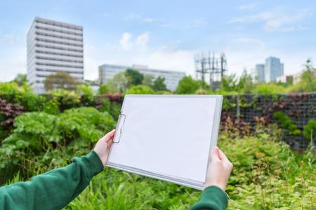 paysagiste: Vue d'une séduisante jeune femme paysagiste travaillant dans un parc public Banque d'images