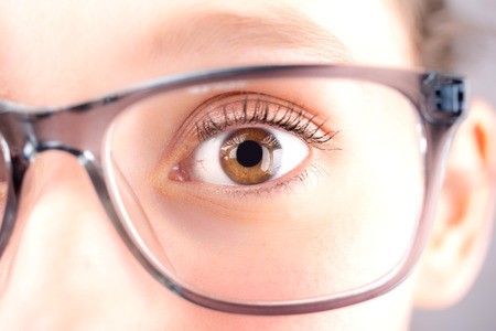 definition high: Detailed close up view of an brown eye behind glasses in high definition Stock Photo