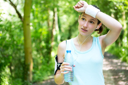 tired person: View of a Young attractive woman drinking water after a running session Stock Photo