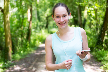 footing: View of a Young attractive woman setting her mobile in armband before running Stock Photo