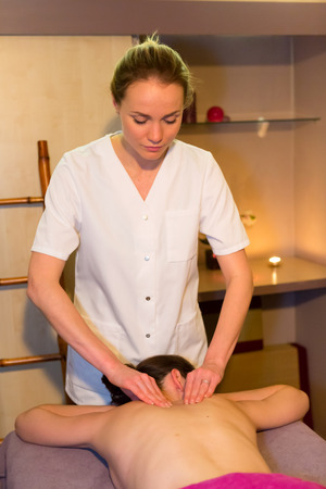 masseuse: View of a Young attractive masseuse doing a massage on a customer Stock Photo