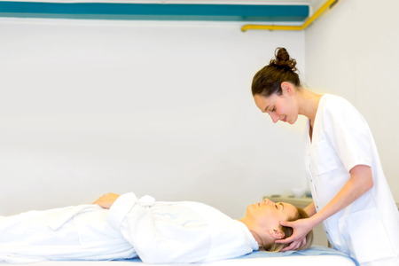 masseuse: View of a Young attractive masseuse doing a capillariy massage Stock Photo