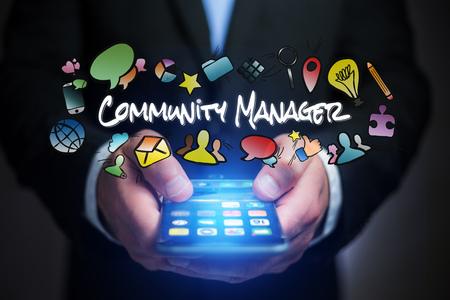 コミュニティ マネージャーのタイトルと飛んでマルチ メディア アイコンを持つスマート フォンを抱きかかえたの概念ビュー 写真素材