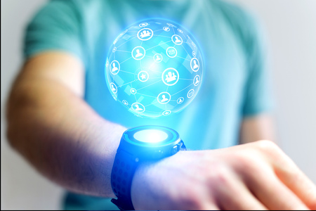 View of a Businessman holding smartwatch with network globe sphere hologram going out - Technology concept Stock Photo
