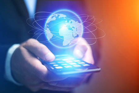 View of a Businessman holding smartphone with globe sphere hologram going out Stock Photo