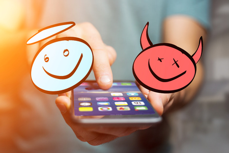 View of Hand drawn angel and devil icon going out a smartphone interface of a man at the office - Ideas concept Stock Photo